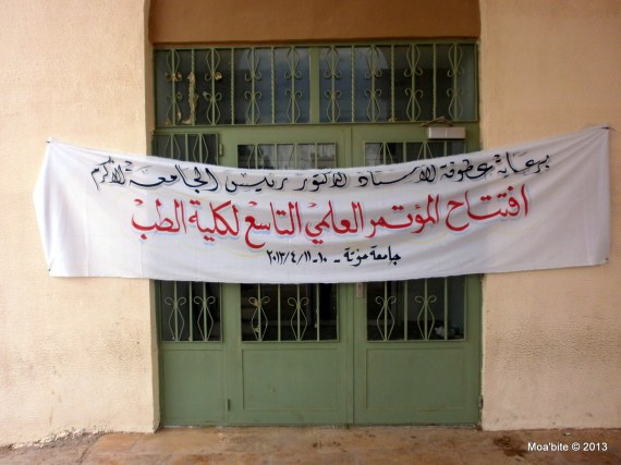 A banner hanged on one of the doors of the basic faculty building: Under the patronage of his Excellency the president of the university of Mu'tah\\ Inauguration of the ninth scientific conference of the faculty of medicine\\ Mu'tah University, 10-11/4/2013.